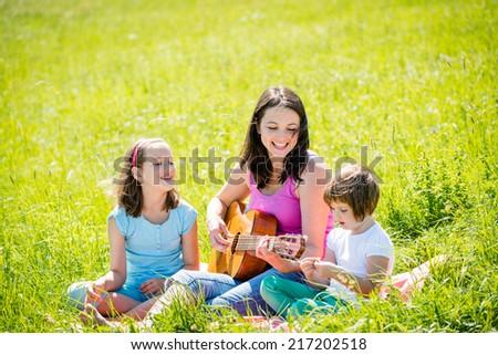 Woman playing guitar to her children in nature on sunny summer day - stock photo