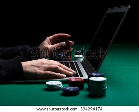 Woman playing online poker with laptop on a green table with chips all around, side view - stock photo