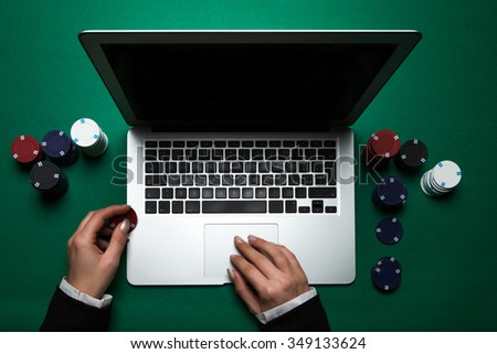 Woman playing online poker with laptop on a green table with chips all around, top view - stock photo