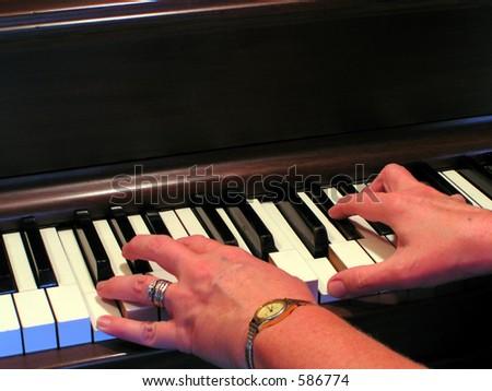 Woman playing piano - stock photo
