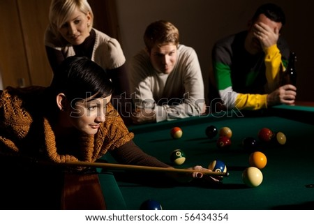 Woman playing snooker, concentrating on ball with cue, friends watching.