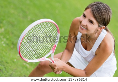 Woman playing tennis and looking very happy - stock photo