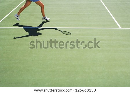 woman playing tennis, only half of her body visible, shadow holding a tennis racket seen on the ground, - stock photo
