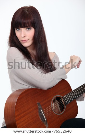 Woman playing the guitar - stock photo