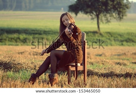 Woman playing the violin at sunrise - stock photo