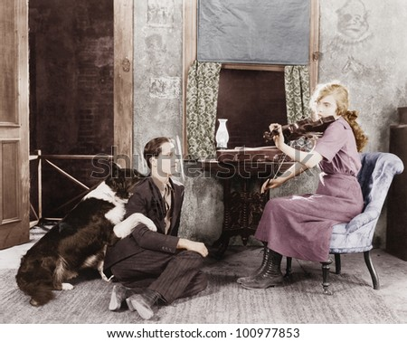 Woman playing the violin for her boyfriend and dog