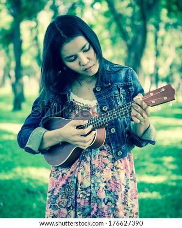 Woman playing ukulele, vintage style. - stock photo