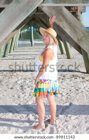 Woman playing under the pier at the beach