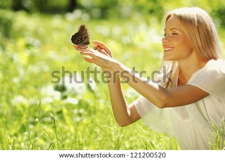 Woman playing with a butterfly on green grass - stock photo