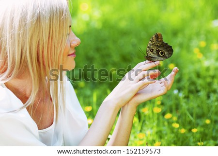 Woman playing with a butterfly on green grass