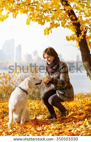 Woman playing with a golden retriever  in autumn park