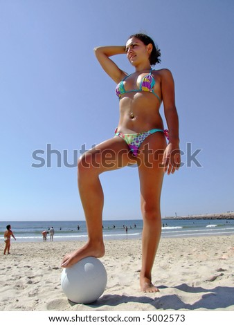 Woman playing with a volleyball in the beach - stock photo