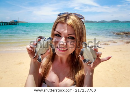 Woman Playing With Baby Sea Turtle On The Beach - stock photo