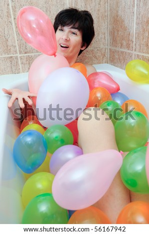 Woman playing with balloons in his bathtub
