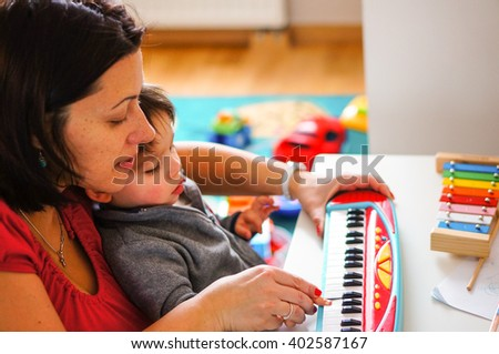 Woman playing with child on a toy piano on table