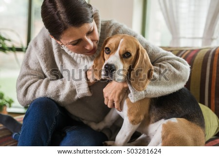 woman playing with dog in her home