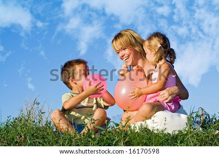 Woman playing with her kids and balloons in the grass outdoors against blue summer sky - stock photo