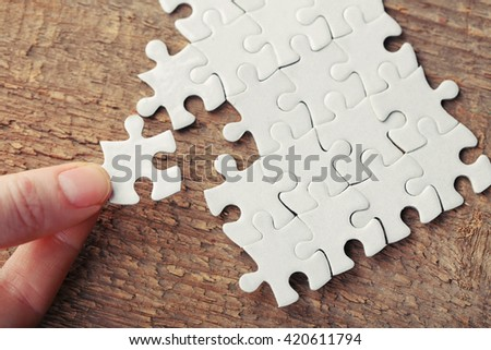 Woman playing with jigsaw puzzle on wooden table - stock photo