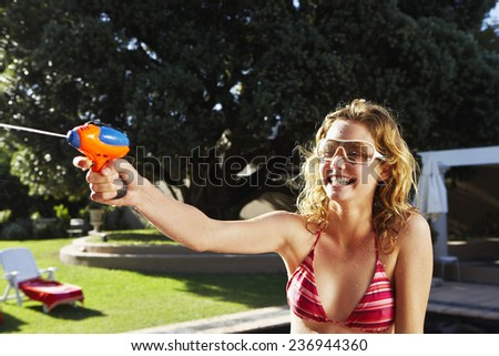 Woman Playing with Water Gun - stock photo