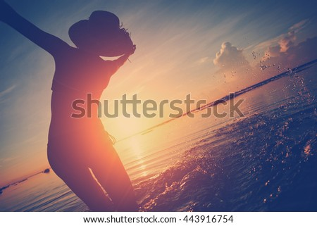 Woman playing with water in the ocean at sunrise (intentional sun glare and vintage color)