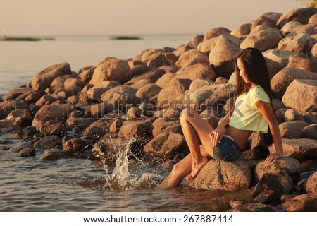 Woman playing with water outdoors - stock photo