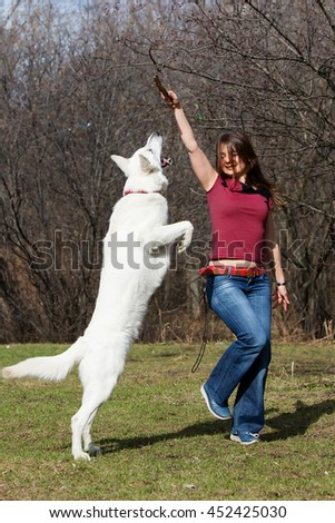 Woman playing with white dog