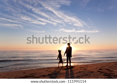 Woman plays with dog on the shore of the lake at sunrise - stock photo