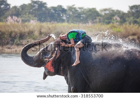 Woman plays with elephant in river - stock photo