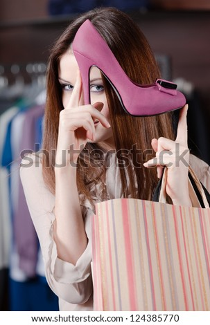 Woman plays with excellent fuchsia shoes at the store - stock photo