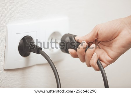 Woman pluging cable to the electric outlet - stock photo
