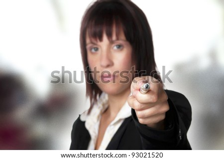 woman point out with a pen in her hand point at the viewer
