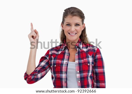 Woman pointing at a copy space against a white background