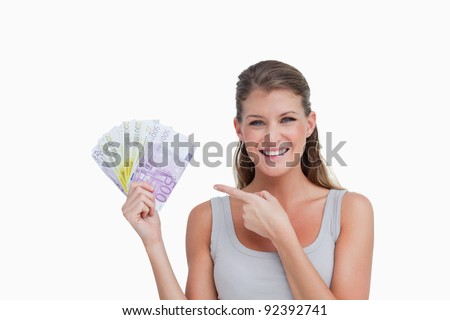 Woman pointing at bank notes against a white background - stock photo