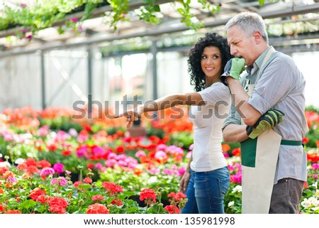 Woman pointing at flowers while asking advice to a gardener