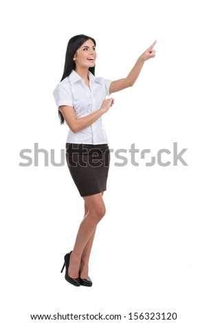 Woman pointing. Full length of beautiful young woman pointing away and smiling while standing isolated on white - stock photo