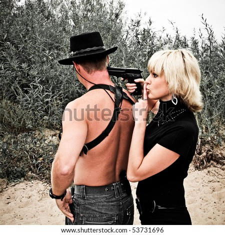 woman pointing gun at shirtless man with revolver wearing cowboy hat, sand and trees on background - stock photo