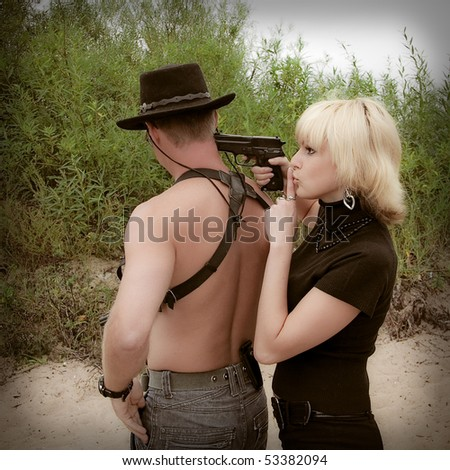 woman pointing gun at shirtless man with revolver wearing cowboy hat, trees on background - stock photo