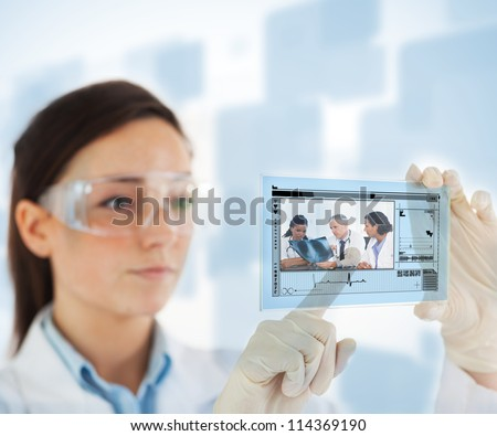 Woman pointing on picture of doctor and nurses loking at x ray on hologram interface on blue and white background
