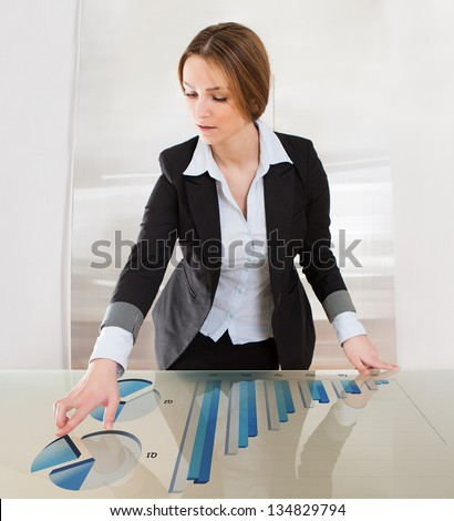 Woman Pointing On Transparent Screen Showing Business Charts - stock photo