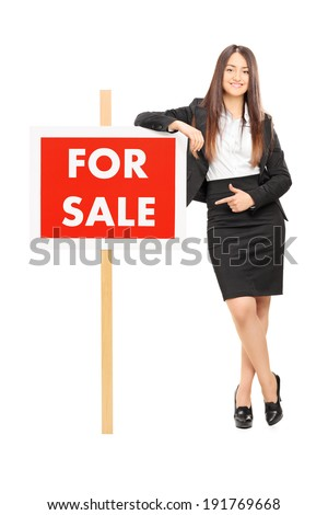 Woman pointing towards a for sale sign isolated on white background - stock photo