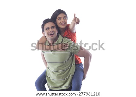 Woman pointing while getting a piggyback ride
