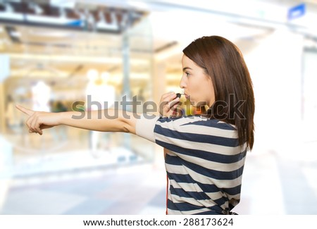 Woman pointing with her finger and using a whistle. Over shopping center background - stock photo
