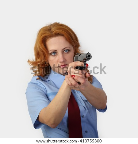 Woman police officer aiming a handgun on gray background in square - stock photo