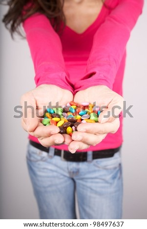 woman portrait holding lot of candy in her hands