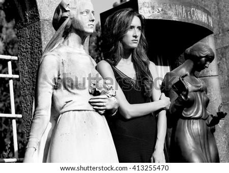 Woman portrait in grief between graveyard women statues monochrome - stock photo