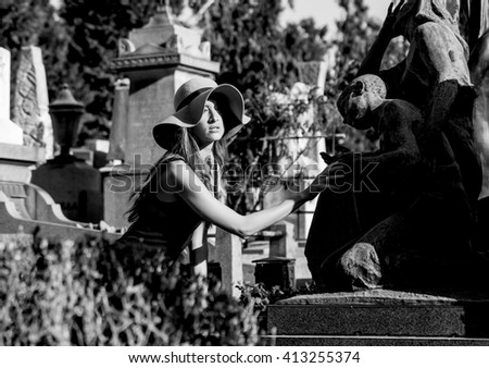 Woman portrait in the graveyard near grave statues monochrome