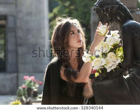 Woman portrait in the graveyard staying with the loved one - stock photo