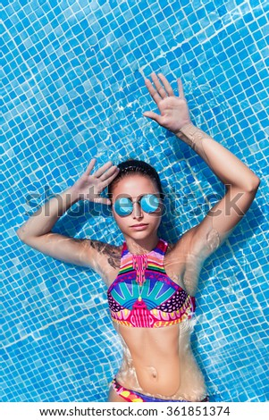 Woman portrait relaxing close to swimming pool at exotic surrounding - stock photo
