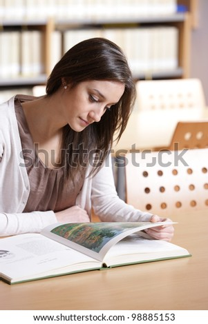 woman portrait: student reading a book at library