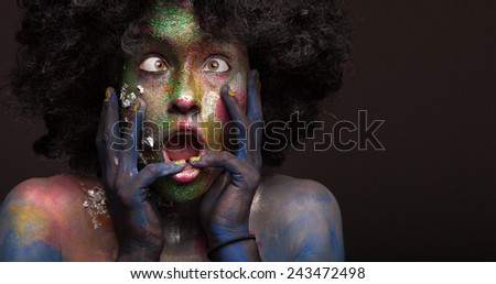 Woman portrait with afro hair style. Face art and body art. Fantasy painted girl smiling. Bright green and violet make up. - stock photo